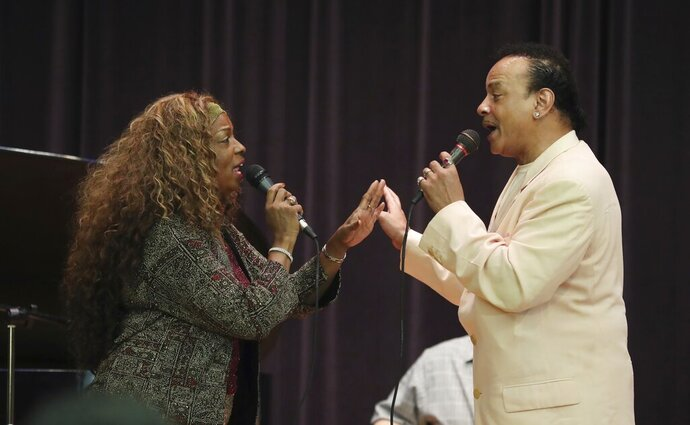 FILE- In this July 31, 2018 file photo, singers Mark Scott of The Miracles and Joan Belgrave, left, perform in Detroit. The Charles H. Wright Museum of African American History is marking Black Music Month with a concert featuring many of Detroit's prominent musical, visual and literary artists. Belgrave is producing and performing at the June 27, 2019 concert,