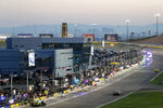 Las Vegas Strip casinos can be seen in the background as drivers make pit stops during a NASCAR Cup Series auto race at the Las Vegas Motor Speedway Sunday, Sept. 26, 2021, in Las Vegas. (AP Photo/Steve Marcus)