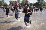 Central American migrants carry children as they run across the Suchiate River from Guatemala to Mexico, near Ciudad Hidalgo, Mexico, Monday, Jan. 20, 2020. More than a thousand Central American migrants hoping to reach United States marooned in Guatemala are walking en masse across a river leading to Mexico in an attempt to convince authorities there to allow them passage through the country. (AP Photo/Santiago Billy)