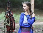 Climate activist Greta Thunberg stands near climbing gear during a visit at the ancient Hambach Forest near the city of Kerpen in western Germany, Aug. 10, 2019. The teenage activist who is a leading figure in the Fridays for Future strikes against climate said that seeing the open-cast lignite pit in Hambach disturbed her deeply and that the time has come to stop talking and take action. (Oliver Berg/dpa via AP)