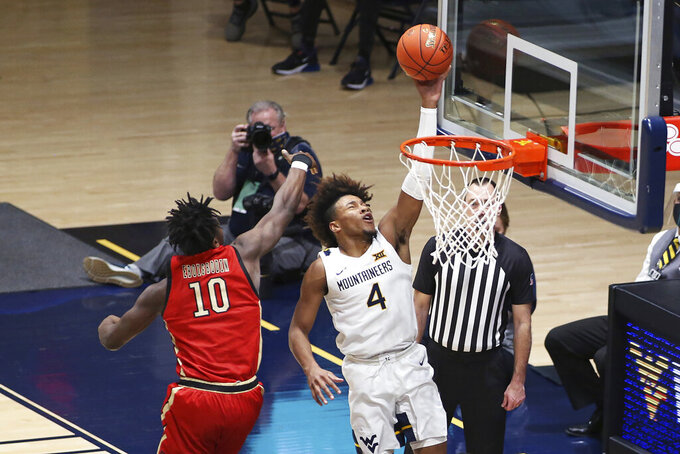 West Virginia guard Miles McBride (4) shoots while defended by Northeastern forward Greg Eboigbodin (10) during the second half of an NCAA college basketball game Tuesday, Dec. 29, 2020, in Morgantown, W.Va. (AP Photo/Kathleen Batten)