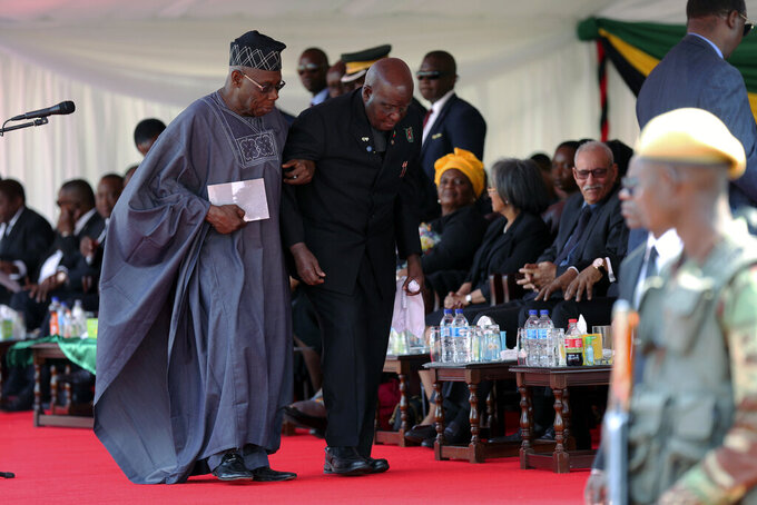 FILE - In this Saturday Sept. 14, 2019 file photo, former Zambia President Kenneth Kaunda is supported by former Nigerian President Olusegan Obasanjo, left, at the state funeral of former Zimbabwean leader, Robert Mugabe in Harare, Zimbabwe. Zambia's first president Kenneth Kaunda has died at the age of 97, the country's president Edward Lungu announced Thursday June 17, 2021. (AP Photo/Tsvangirayi Mukwazhi, File)