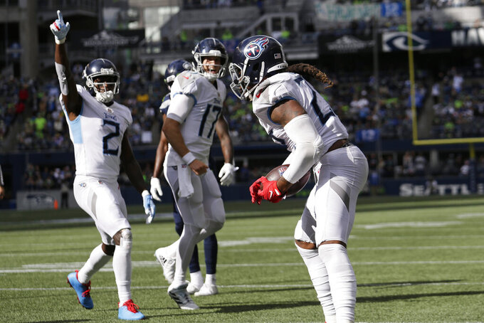 Tennessee Titans running back Derrick Henry, right, reacts with wide receiver Julio Jones (2) and quarterback Ryan Tannehill (17) after Henry rushed for a touchdown against the Seattle Seahawks during the second half of an NFL football game, Sunday, Sept. 19, 2021, in Seattle. (AP Photo/John Froschauer)