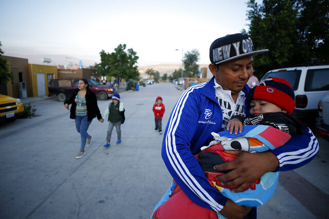 In this July 10, 2019, photo, Juan Carlos Perla carries his youngest son, Joshua Mateo Perla, as the family leaves their home in Tijuana, Mexico, for an asylum hearing in San Diego. They were among the first sent back to Mexico under a Trump administration policy that dramatically reshaped the scene at the U.S.-Mexico border by returning migrants to Mexico to wait out their U.S. asylum process.  (AP Photo/Gregory Bull)