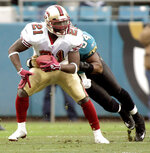 FILE - In this Dec. 18, 2005, file photo, San Francisco 49ers running back Frank Gore, left, is tackled by Jacksonville Jaguars defender Mike Peterson, right, during the second quarter of an NFL football game in Jacksonville, Fla. Gore took his first NFL snaps as a pro with the 49ers in 2005 in what seems like a lifetime ago for the NFL's third-leading rusher. It all comes full circle for the 37-year-old Gore on Sunday, Sept. 20, 2020, when his New York Jets host the team with which he began his career 16 years ago. (AP Photo/Phil Coale, File)
