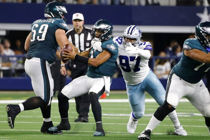 Philadelphia Eagles center Landon Dickerson (69) looks on as quarterback Jalen Hurts (1) is sacked by Dallas Cowboys defensive tackle Osa Odighizuwa (97) in the first half of an NFL football game in Arlington, Texas, Monday, Sept. 27, 2021. (AP Photo/Michael Ainsworth)