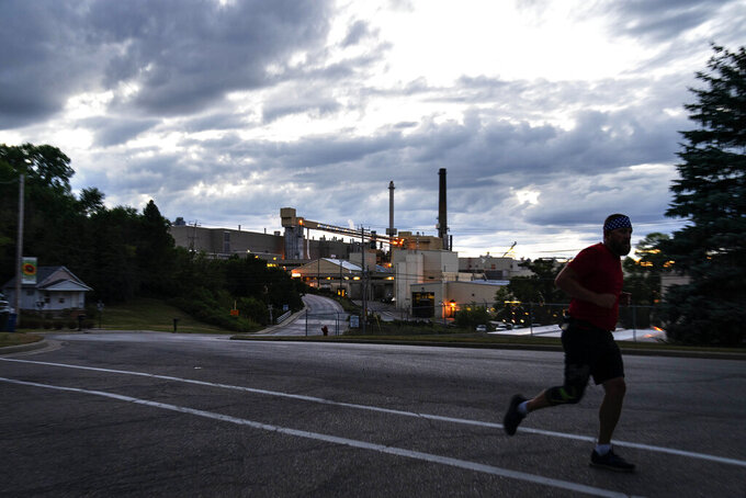 CORRECTS CITY TO COMBINED LOCKS, WIS. A jogger runs past the Midwest Paper Group mill in Combined Locks, Wis., part of the greater Appleton area, Monday, Aug. 17, 2020. By almost any measure, President Donald Trump's promises of an economic revival in places like Appleton have gone unfulfilled. The area has lost about 8,000 jobs since he got elected. The state that is vital for Trump's victory had more jobs a decade ago when the country was still ailing from the Great Recession than it did in July.(AP Photo/David Goldman)