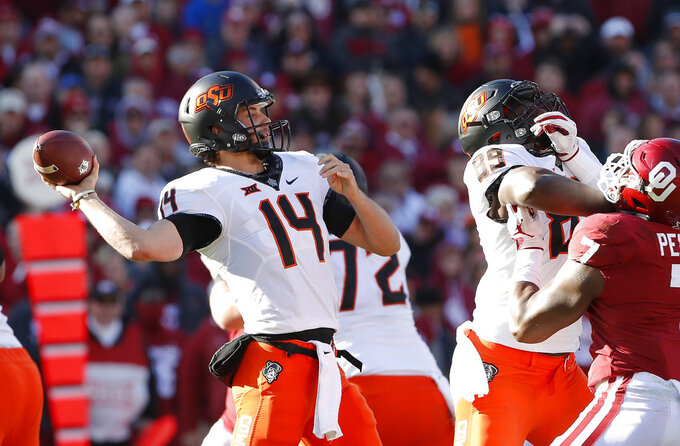 Oklahoma State quarterback Taylor Cornelius (14) passes against Oklahoma in the first half of an NCAA college football game in Norman, Okla., Saturday, Nov. 10, 2018. (AP Photo/Alonzo Adams)