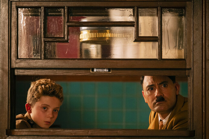 This image released by Fox Searchlight Pictures shows, from left, Roman Griffin Davis and Taika Waititi in a scene from the WWII satirical film