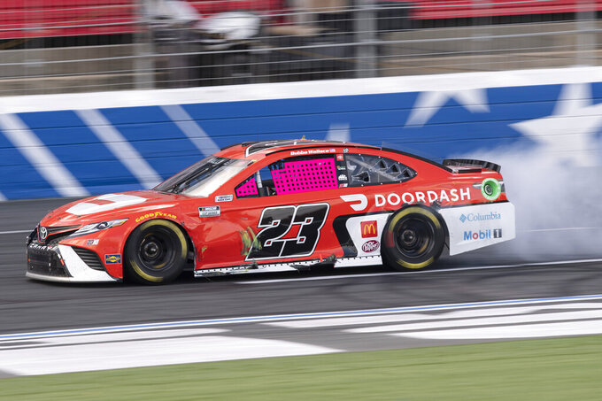 Bubba Wallace (23) restarts his car after stalling during a NASCAR Cup Series auto racing race at Charlotte Motor Speedway, Monday, Oct. 11, 2021, in Concord, N.C. (AP Photo/Matt Kelley)