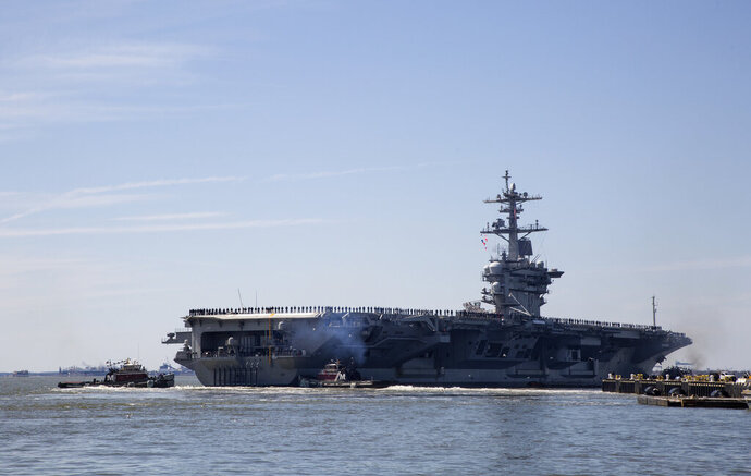 FILE - In this April 1, 2019, file photo, the USS Abraham Lincoln deploys from Naval Station Norfolk, in the vicinity of Norfolk, Va. The White House said Sunday, May 5, that the U.S. is deploying military resources to send a message to Iran. White House national security adviser John Bolton said in a statement that the U.S. is deploying the USS Abraham Lincoln Carrier Strike Group and a bomber task force to the U.S. Central Command region, an area that includes the Middle East. (Kaitlin McKeown/The Virginian-Pilot via AP, File)