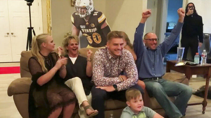 In this still image from video provided by the NFL, Logan Wilson, center, reacts after being selected by the Cincinnati Bengals during the third round of the NFL football draft, Friday, April 24, 2020. (NFL via AP)