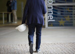 A man carries a hard hat as he walks into the entrance of EU headquarters in Brussels, Thursday, Oct. 3, 2019. Several European Union leaders have declared that the measures presented by British Prime Minister Boris Johnson could fall short of the concessions necessary to forge a deal that would allow both side to part ways with an amicable deal at the end of the month.(AP Photo/Virginia Mayo)