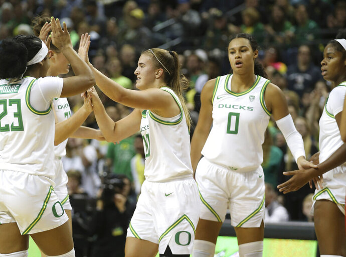 Oregon's Sabrina Ionescu, center, celebrates a play with teammates during the first half of the team's exhibition basketball game against U.S. team in Eugene, Ore., Saturday, Nov. 9, 2019. (AP Photo/Chris Pietsch)
