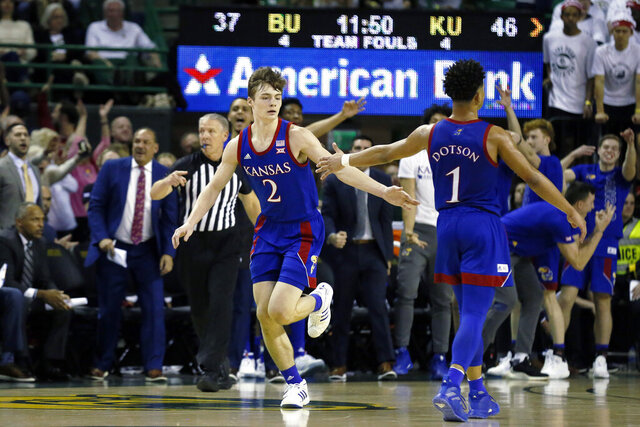 FILE - Kansas guard Christian Braun (2) is congratulated by teammate Devon Dotson after a three-point basket during an NCAA college basketball game against Baylor in Waco, Texas, in this  Saturday, Feb. 22, 2020, file photo. Sophomore guard Christian Braun is one of the Big 12's best sharpshooters. (AP Photo/Ray Carlin, File)