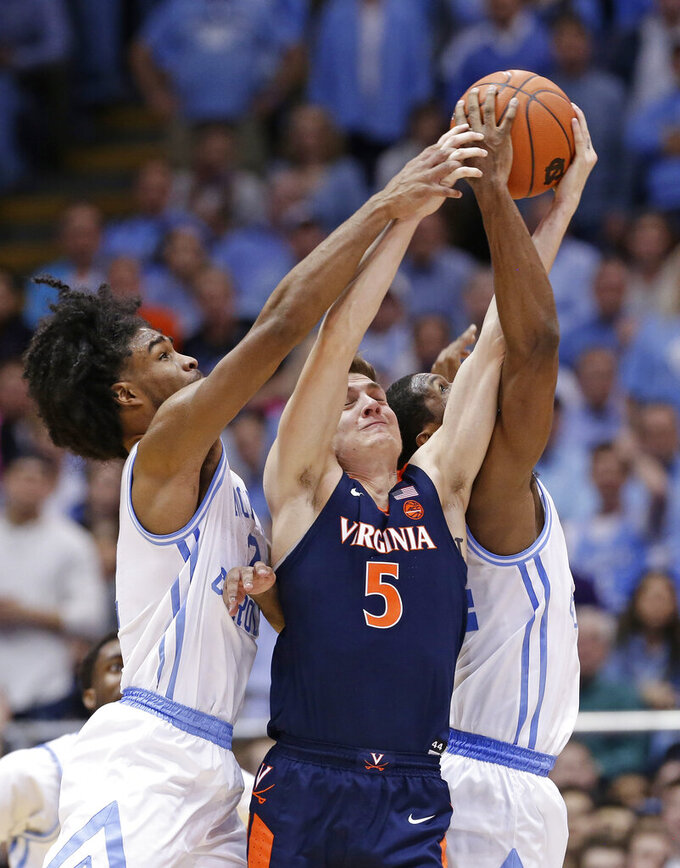 North Carolina's Coby White and Kenny Williams, right, reach for the ball with Virginia's Kyle Guy (5) during the second half of an NCAA college basketball game in Chapel Hill, N.C., Monday, Feb. 11, 2019. Virginia won 69-61. (AP Photo/Gerry Broome)