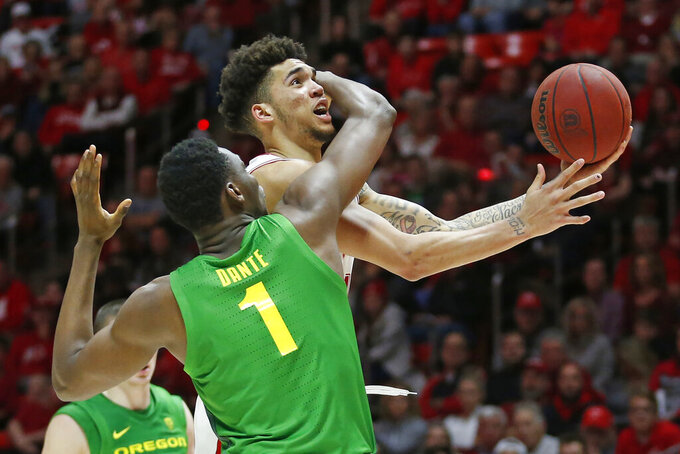 Utah forward Timmy Allen, rear, is fouled by Oregon center N'Faly Dante (1) as he drives to the basket in the second half during an NCAA college basketball game Saturday, Jan. 4, 2020, in Salt Lake City. (AP Photo/Rick Bowmer)