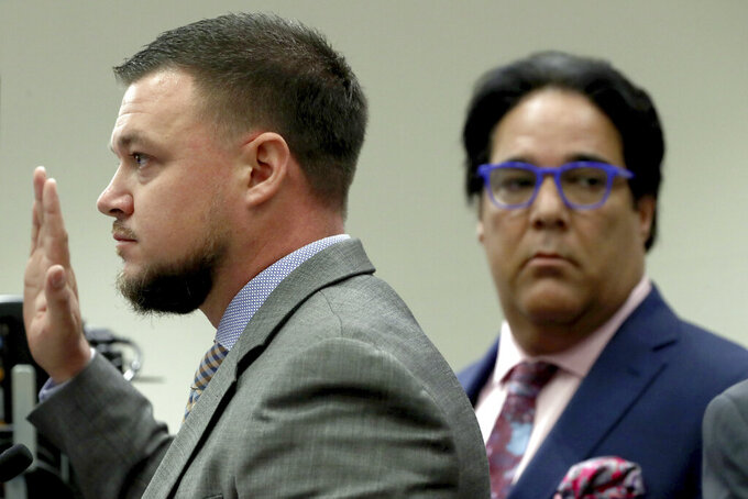 Hollywood Police detective Steven Regentz, left, is sworn in to testify during a first appearance hearing for NFL free agent Antonio Brown, Friday, Jan. 2,4 0202, at the Broward County Courthouse in Fort Lauderdale, Fla. Brown was granted bail on Friday after turning himself in at a Florida jail on charges that he and his trainer attacked the driver of a moving truck that carried some of his possessions from California.  (Amy Beth Bennett/South Florida Sun Sentinel via AP, Pool)