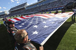 Pit crew members unfurl a United States flag prior to the national anthem before a NASCAR Cup Series auto race at Charlotte Motor Speedway in Concord, N.C., Sunday, May 30, 2021. (AP Photo/Nell Redmond)