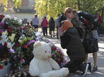 A woman prays near a memorial to the people killed during an attack in the vocational college in Kerch, Crimea, Thursday, Oct. 18, 2018. An official says that authorities on the Crimean Peninsula are searching for a possible accomplice of the student who carried out an attack on a vocational school, killing 20 people and wounding more than 50 others. (AP Photo/Str)