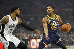 Utah Jazz guard Donovan Mitchell, right, tries to drive by Los Angeles Clippers forward Paul George during the first half of an NBA basketball game Saturday, Dec. 28, 2019, in Los Angeles. (AP Photo/Mark J. Terrill)