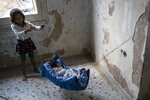 A two-month old baby from Afghanistan sleeps at an abandoned building near Mytilene town, on the northeastern island of Lesbos, Greece, Tuesday, Sept. 15, 2020.  Just over 6% of people have been rehoused, following a recent fire that destroyed Greece's biggest camp for refugees and migrants making 12,500 people homeless, in a new temporary facility under construction on the island of Lesbos. (AP Photo/Petros Giannakouris)