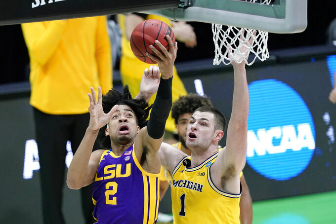 LSU forward Trendon Watford (2) drives to the basket ahead of Michigan center Hunter Dickinson (1) during the first half of a second-round game in the NCAA men's college basketball tournament at Lucas Oil Stadium Monday, March 22, 2021, in Indianapolis. (AP Photo/AJ Mast)