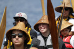 Canoe pullers wait to ask permission to land from the host Muckleshoot tribe during a stop on the annual tribal canoe journey through the Salish Sea Thursday, July 18, 2019, in Seattle. About 20 canoes from Northwest Native coastal tribes landed Thursday at Alki Beach on one of several legs of the canoe journey that gathers other canoe families from host tribes as they travel to a final landing, this year near Bellingham, Wash., at the Lummi Nation. (AP Photo/Elaine Thompson)