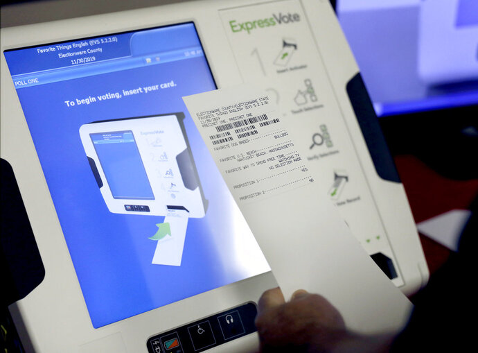 FILE - This Oct. 19, 2017, file photo shows a new voting machine which prints a paper record on display at a polling site in Conyers, Ga. Georgia officials have estimated it could cost over $100 million to adopt the machines statewide. (AP Photo/David Goldman, File)