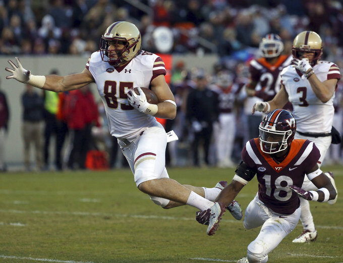 Korab Idrizi (85) of Boston College escapes the grasp of Virginia Tech defender Tyree Rodgers (18) for a 22 yard touchdown in the second half of an NCAA college football  game in Blacksburg Va., Saturday, Nov. 3 2018. Boston College won the game 31-21. (Matt Gentry/The Roanoke Times via AP)