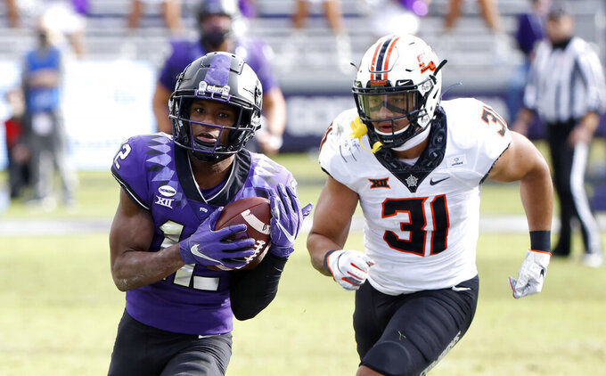 TCU wide receiver Derius Davis (12) gets past Oklahoma State safety Kolby Harvell-Peel (31) to score a touchdown during the second half of an NCAA college football game Saturday, Dec. 5, 2020, in Fort Worth, Texas. TCU won 29-22. (AP Photo/Ron Jenkins)