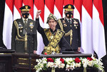 In this photo released by Indonesian Presidential Palace, Indonesian President Joko Widodo, center, dressed in a traditional outfit, raises his fist as he delivers his national address before the parliament members in Jakarta, Indonesia, Friday, Aug. 14, 2020. Indonesia's president called on all citizens to turn the COVID-19 crisis into an advancement opportunity and pledged health care reforms in an address Friday ahead of the country's 75th anniversary of independence. (Agus Suparto/Presidential Palace via AP)