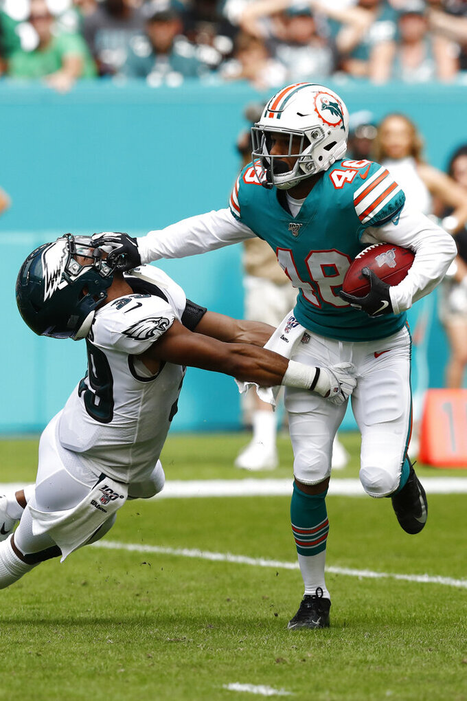 Miami Dolphins defensive back Marcus Sherels (48) stops a tackle by Philadelphia Eagles defensive back Craig James (39), during the first half at an NFL football game, Sunday, Dec. 1, 2019, in Miami Gardens, Fla. (AP Photo/Brynn Anderson)