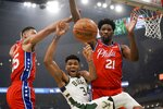 Milwaukee Bucks' Giannis Antetokounmpo is fouled as he drives between Philadelphia 76ers' Ben Simmons and Joel Embiid (21) during the first half of an NBA basketball game Saturday, Feb. 22, 2020, in Milwaukee. (AP Photo/Morry Gash)