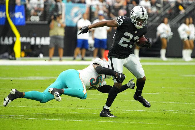 Miami Dolphins middle linebacker Elandon Roberts (52) attempts to tackle Las Vegas Raiders running back Kenyan Drake (23) during the first half of an NFL football game, Sunday, Sept. 26, 2021, in Las Vegas. (AP Photo/Rick Scuteri)