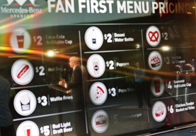FILE - In this May 16, 2016, file photo, Atlanta Falcons president and CEO Rich McKay is reflected in a screen displaying the proposed concession stand menu prices inside Mercedes-Benz Stadium, home of the Falcons in Atlanta. The crippling grip the coronavirus pandemic has had on the sports world has forced universities, leagues and franchises to evaluate how they might someday welcome back fans. which thousands could be in close proximity. They gather in concourses to chat, buy food and drinks and await the start. They stand in lines at restrooms at halftime or between innings. Then they surge toward the exits at the final whistle or last out. (AP Photo/David Goldman, File)