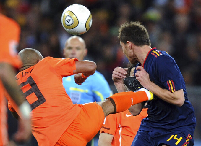 FILE - In this Sunday, July 11, 2010, file photo, Netherlands' Nigel de Jong, left, fouls Spain's Xabi Alonso during the World Cup final soccer match between the Netherlands and Spain at Soccer City in Johannesburg, South Africa. Violence is part of the game in many sports. But when the Cleveland's Myles Garrett ripped the helmet off Mason Rudolph and hit the Pittsburgh Steelers' quarterback in the head with it, the Browns' defender crossed a line _ one that attracts the attention of authorities sometimes from within their sport and in other cases from criminal prosecutors. (AP Photo/Daniel Ochoa de Olza, File)