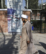 In this Tuesday, Oct. 15, 2019 photo, a Shiite Muslim cleric walks past anti-U.S. graffiti on the wall of the former U.S. Embassy, in Tehran, Iran. For those who were there, the memories are still fresh 40 years after one of the defining events of Iran's 1979 Islamic Revolution, when protesters seized the U.S. Embassy in Tehran and set off a 444-day hostage crisis whose consequences continue to reverberate to this day. (AP Photo/Vahid Salemi)