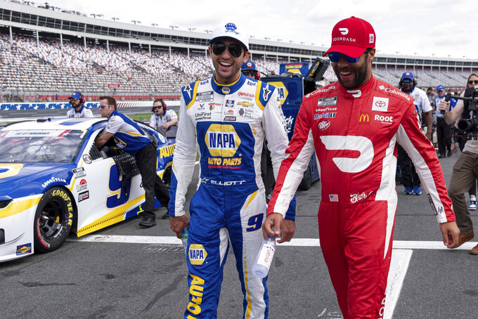 Chase Elliott, left, and Bubba Wallace joke around before qualifying for the NASCAR Cup Series auto race at Charlotte Motor Speedway on Saturday, May 29, 2021 in Charlotte, N.C. (AP Photo/Ben Gray)