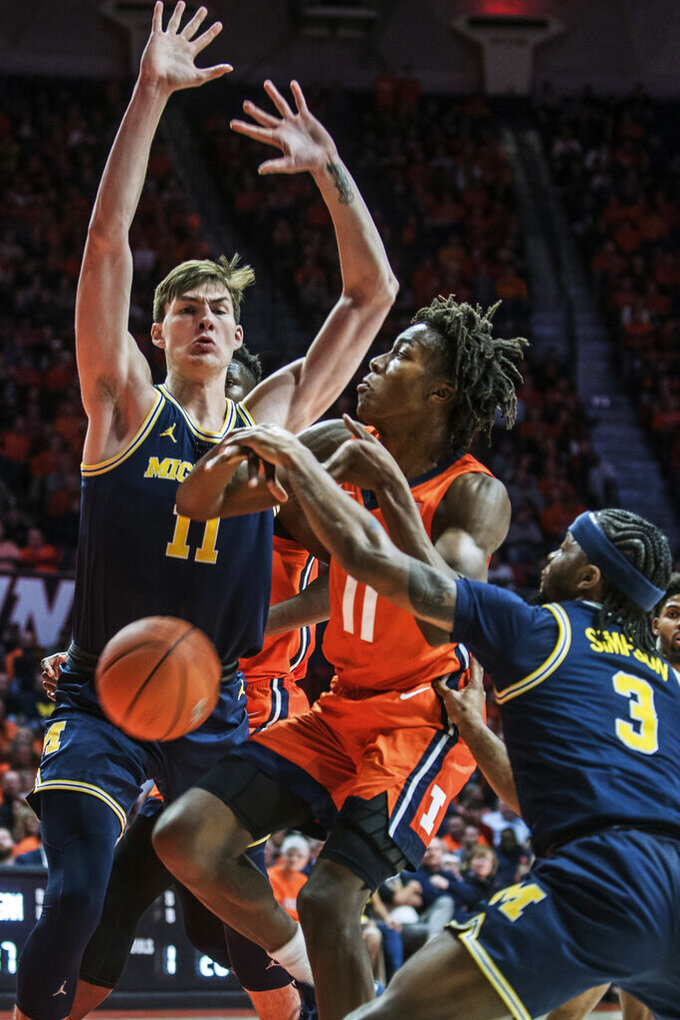 Illinois' Ayo Dosunmu (11) has the ball knocked loose by Michigan's Zavier Simpson (3) and Colin Castletown (11) in the first half of an NCAA college basketball game, Wednesday, Dec. 11, 2019, in Champaign, Ill. (AP Photo/Holly Hart)