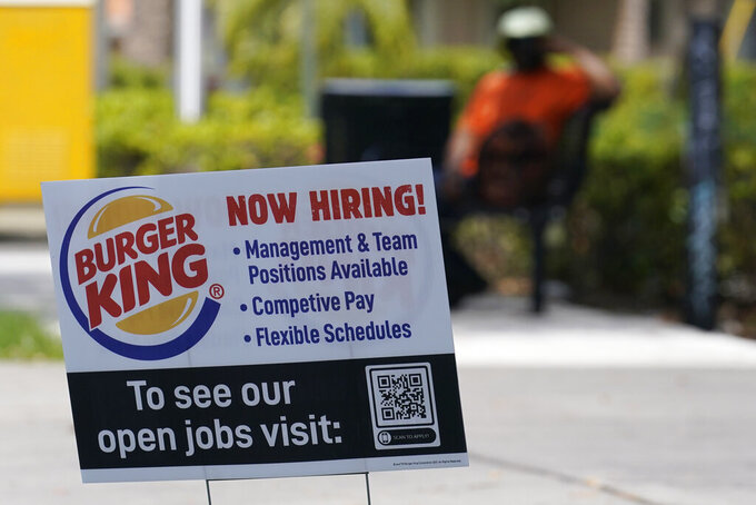 A sign looking for employees to work at Burger King restaurants is posted, Tuesday, April 27, 2021, in Miami.  Restaurant Brands International, the parent company of Burger King, saw its sales climb in the first quarter to top Wall Street's view as Americans made purchases at the burger chain amid easing coronavirus pandemic restrictions.  (AP Photo/Marta Lavandier)