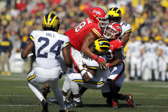 Michigan defensive back Josh Metellus, center bottom, is brought down by Maryland offensive lineman Ellis McKennie (68) and wide receiver Sean Savoy (29) after Metellus intercepted a pass from quarterback Josh Jackson during the first half of an NCAA college football game, Saturday, Nov. 2, 2019, in College Park, Md. (AP Photo/Julio Cortez)