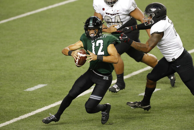 UNLV defensive lineman Adam Plant Jr. (7) pulls down Hawaii quarterback Chevan Cordeiro (12) in the second half of an NCAA college football game Saturday, Dec. 12, 2020, in Honolulu. (AP Photo/Marco Garcia)