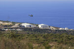 A helicopter flies over a base of the U.N. peacekeeping force, in the southern town of Naqoura, Lebanon, Wednesday, Oct. 14, 2020. Lebanon and Israel are to begin indirect talks Wednesday over their disputed maritime border, with American officials mediating the talks that both sides insist are purely technical and not a sign of any normalization of ties. (AP Photo/Bilal Hussein)