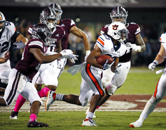Auburn wide receiver Ryan Davis (23) runs after a pass reception while being pursued by Mississippi State defenders during the second half of their NCAA college football game in Starkville, Miss., Saturday, Oct. 6, 2018. Mississippi State won 23-9. (AP Photo/Rogelio V. Solis)
