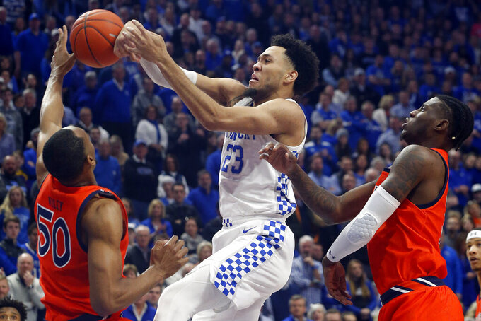 Kentucky's EJ Montgomery, center, struggles between Auburn's Austin Wiley (50) and Danjel Purifoy, right, during the first half of an NCAA college basketball game in Lexington, Ky., Saturday, Feb. 29, 2020. (AP Photo/James Crisp)