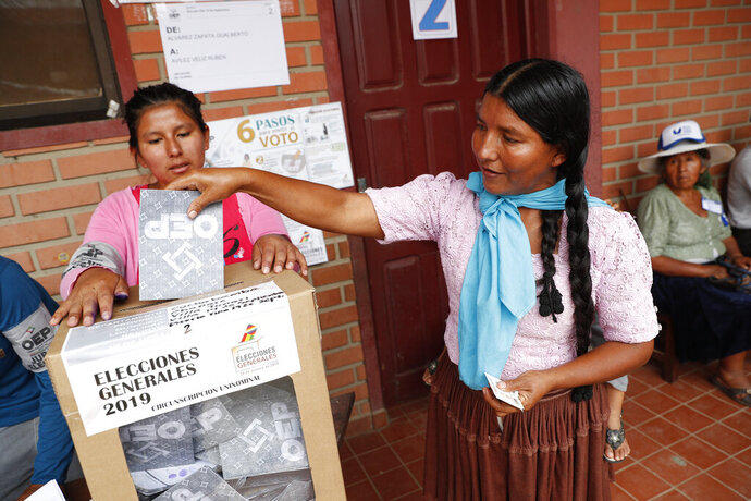 A woman casts her vote in Villa 14 de Septiembre, in the Chapare region, Bolivia, Sunday, Oct. 20, 2019. Bolivians are voting in general elections Sunday where Bolivia's President Evo Morales is candidate for a fourth term. (AP Photo/Juan Karita)