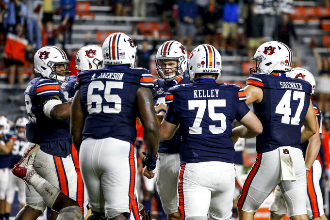 Auburn's Anders Carlson (26) celebrates with teammates after kicking the go-ahead field goal against Arkansas during the second half of an NCAA college football game Saturday, Oct. 10, 2020, in Auburn, Ala. Auburn won 30-28. (AP Photo/Butch Dill)