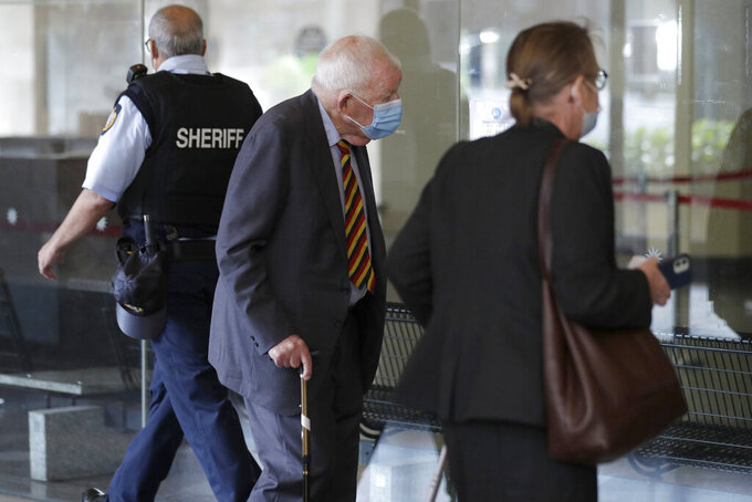 New Zealand businessmen Ron Brierley, center, arrives at the Local Downing Centre Court in Sydney, Thursday, Oct. 14, 2021, to be sentenced for possessing child sex abuse images. Brierley, one of New Zealand's most well-known businessmen, was sentenced to 14 months in prison for possessing child sex abuse images. (AP Photo/Rick Rycroft)
