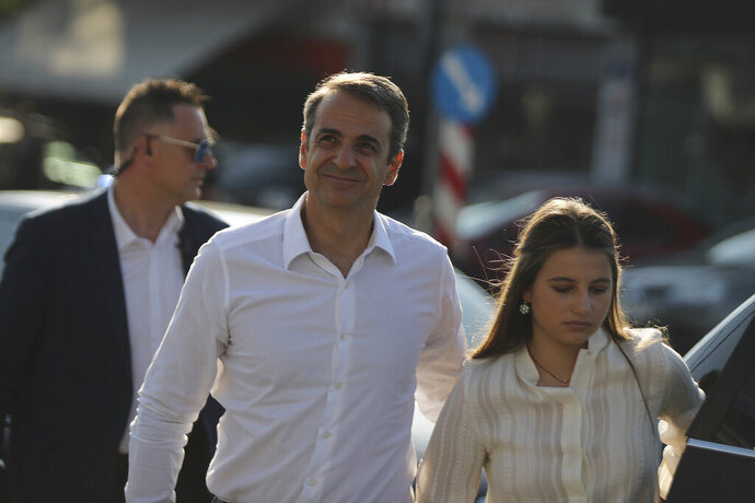 Greek opposition New Democracy conservative party leader Kyriakos Mitsotakis with his daughter Dafni arrive at the New Democracy headquarters in Athens, on Sunday, July 7, 2019. Exit polls in Greece's general election indicate conservative opposition leader Kyriakos Mitsotakis has won a comfortable victory over left-wing Prime Minsiter Alexis Tsipras. (AP Photo/Petros Giannakouris)